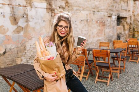 Smiling girl with long curly hair holding bag full of food from market and posing self-consciously. Cute young woman  leaned wearily against the fence after shopping. Purchase of products, buying meal