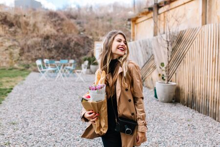 Pretty white european girl in trendy brown coat returns from shopping with purchases in paper bag. Charming young woman with a professional camera gladly posing on the outskirts of the city Stock fotó