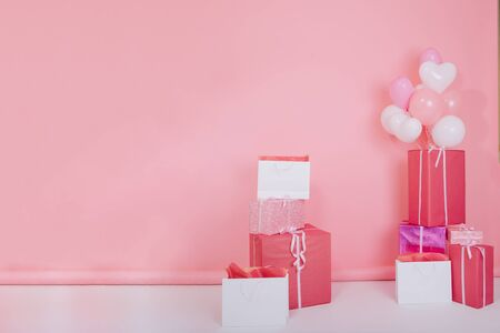 Photo of big bright presents and white party balloons for birthday standing on the floor. Colorful gift boxes with cute ribbons for christmas or st. valentines day isolated on rose-colored background