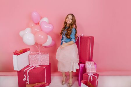 Smiling birthday girl in stylish attire with trendy hairstyle received many gifts for her jubilee. Portrait of fascinating curly young woman posing with present boxes at her party on pink background
