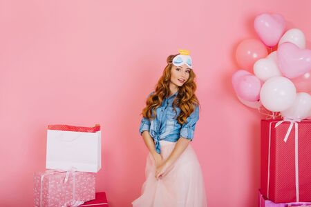 Portrait of adorable birthday girl with surprised face expression standing next to gift boxes. Charming curly young woman in lush skirt and denim shirt planning surprise party with presents for friend