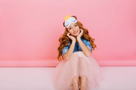 Lovely lady with long curly hair sitting on the floor in pink room propped face with hands and smiling. Charming girl in lush skirt with trendy hairstyle posing indoors on rose-colored background Zdjęcie Seryjne