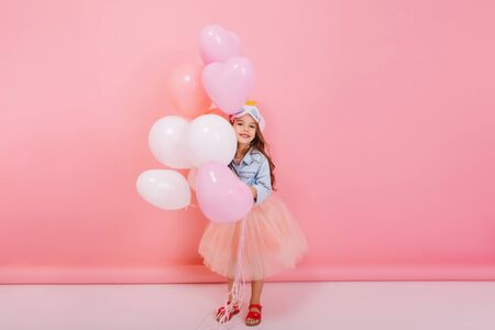 Joyful little girl in tulle skirt smiling to camera, having fun with flying balloons on pink background. Having birthday mood of pretty child, stylish outlook, expressing positivity