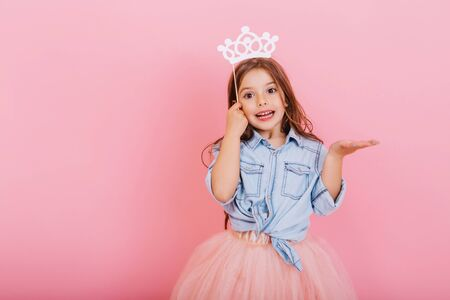 Joyful little girl with long brunette hair in tulle skirt holding princess crown on head isolated on pink background. Celebrating brightful carnival for kids, expressing positivity of birthday party Banco de Imagens