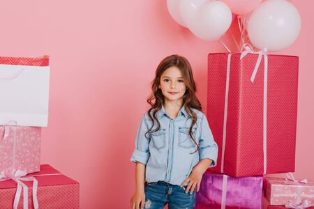 Joyful little girl in blue shirt smiling to camera on big giftboxes with balloons background. Pink colors, birthday mood of pretty child, stylish outlook, expressing positivity
