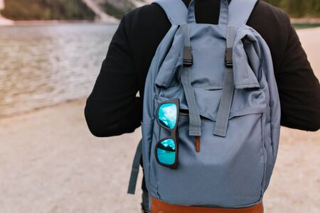 Man wearing cotton black sweater standing in front of lake with stylish travel bag and sunglasses. Outdoor portrait of guy carrying big blue backpack walking near river with rucksack on foreground. 版權商用圖片