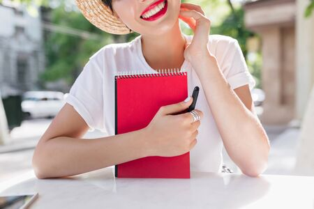 Excited joyful girl with red planner book chilling in outdoor cafe in summer morning, creating poetry during lunch. Close-up portrait of smiling young woman in straw hat sitting at the table.
