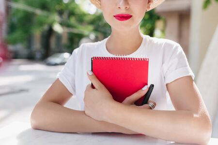 Close-up portrait of woman with lightly tanned skin and elegant manicure holding cute notebook and pen. Beautiful girl with red lips wears silver ring chilling in outdoor cafe with diary book.