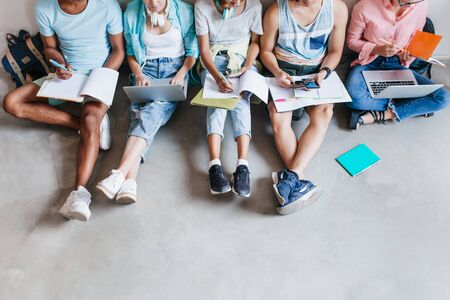Overhead portrait of students in trendy sneakers chilling on the floor while preparing for exams together. University friends spending time together using laptops and writing abstract. Foto de archivo