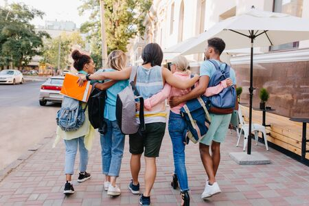 Portrait from back of students with stylish backpacks walking down the street after lectures in university. Tall brunette young man embracing girls while spending time with them outdoot.