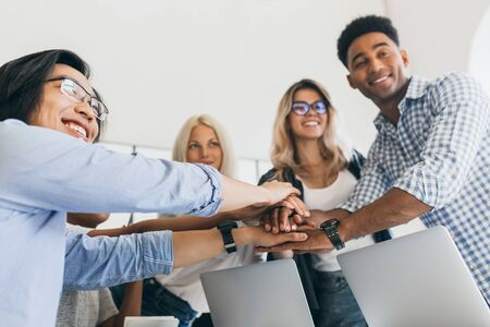 Portrait of asian office worker in glasses holding hands with adrican and european colleagues. Indoor photo of teambuilding and smiling young people with laptops. Stock Photo