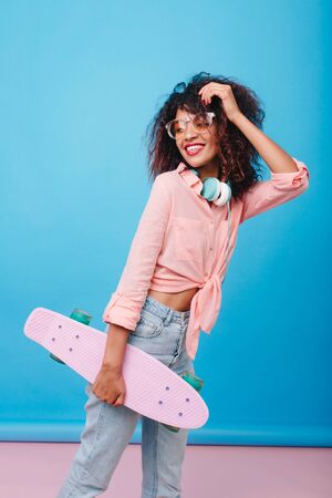Sporty laughing african girl in jeans holding longboard and looking away. Indoor portrait of slim mulatto young woman in cotton shirt posing with pleasure in studio with bright interior.