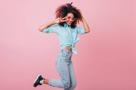 Terrific dark-haired lady in trendy jeans dancing with hands up. Amazing black young woman with brown curls enjoying photoshoot on pink background. Stockfoto
