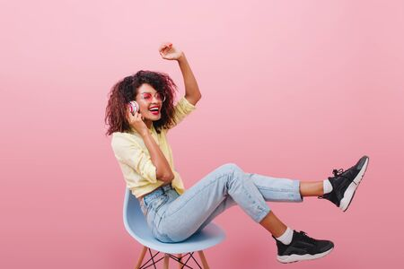 Slim african woman with long legs listening music and laughing. Stunning mulatto female model in black shoes sitting on blue chair in pink studio. Stock Photo - 140199841