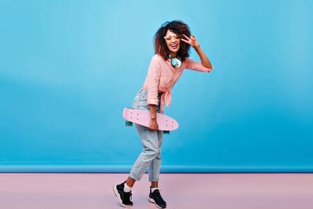 Full-length portrait of curly mulatto girl in black sneakers posing with peace sign after skating. Indoor photo of excited african lady with skateboard standing in front of blue wall with smile.