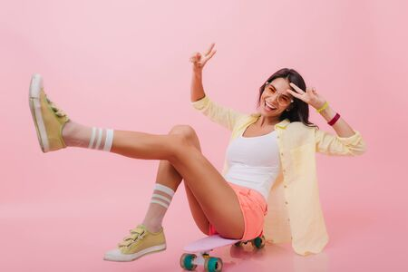 Enthusiastic hispanic girl in trendy yellow jacket sitting on longboard with legs up. Joyful latin woman in colorful bracelets laughing during photoshoot in pink studio.