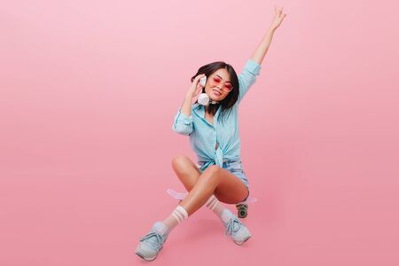 Pretty dark-haired european girl in blue clothes sitting with legs crossed. Indoor portrait of fashionable brunette caucasian woman in street outfit posing on pink background.