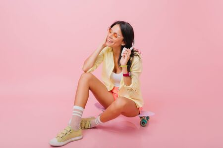 Spectacular hispanic femame model with trendy hairstyle sitting with legs crossed on longboard. Elegant asian girl in yellow attire gently smiling while posing in studio with cute pink interior.