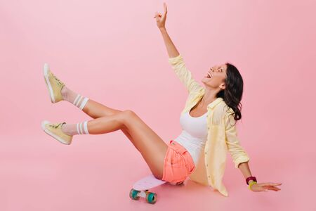 Relaxed girl in bright summer outfit sitting on skateboard with legs up and laughing. Beautiful young brunette lady in yellow shoes spending time in studio with longboard. Stock Photo