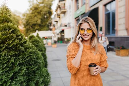 Laughing pretty lady talking on phone while walking by bushes with cup of tea. Outdoor portrait of ecstatic blonde woman in orange sweater spending time at the street and waiting friend with coffee. Standard-Bild - 140454313
