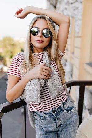 Amazing white girl in vintage jeans posing with pleasure and showing arm tattoo. Portrait of graceful fair-haired woman in sunglasses resting in morning at balcony. Standard-Bild - 140453050