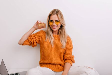 Pretty young woman with sly smile holding bank card, sitting with laptop. Excited fair-haired girl in round sunglasses going to online shopping during rest in home. Standard-Bild - 140453099
