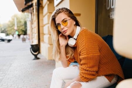 Pretty lady in white jeans and brown cardigan looking with interested smile while resting on bench. Outdoor portrait of stylish girl in ripped denim pants sitting beside cafe. Standard-Bild - 140454259