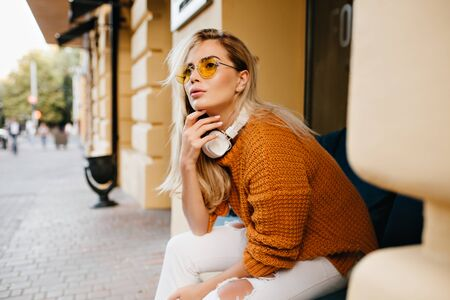 Pensive pale girl in vintage brown sweater touching chin with fingers and looking up. Outdoor portrait of stylish lady in white headphones sitting on the street and waiting friend. Standard-Bild - 140454389