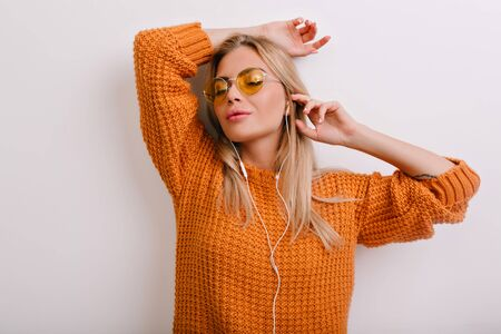 Inspired girl in oversize wool sweater relaxing with eyes closed, leaning to the wall. Indoor portrait of dreamy blonde woman in glasses and earphones isolated on white background. Standard-Bild - 140454525