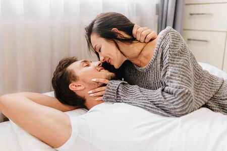 Charming dark-haired lady with long white nails touching husbands face in morning. Indoor photo of magnificent young woman in soft sweater chilling with boyfriend in bedroom.
