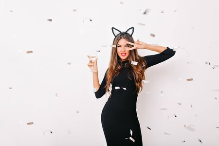 Playful young woman with wineglass posing with pleasure at party. Debonair long-haired girl drinking champagne under confetti. Reklamní fotografie