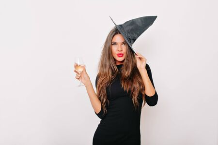 Pretty woman in carnival hat drinking champagne. Stylish glamorous girl enjoying wine in halloween. Reklamní fotografie