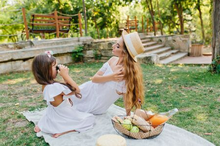 Portrait of little female photographer having fun with mom in park in weekend with basket of meal on foreground. Brunette girl standing on knees and making photo of her beautiful mother in white dress