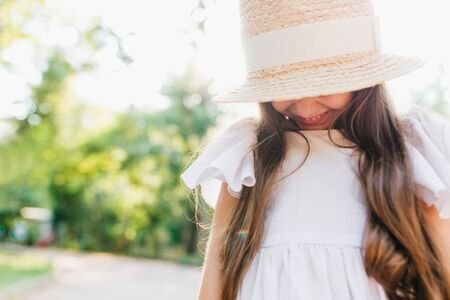 Elegant little lady wearing boater decorated with ribbon looking down and smiling. Close-up portrait of long-haired brunette girl hiding her face under straw hat in park.
