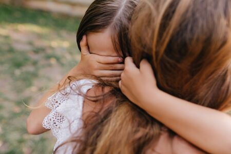 Sad dark-haired girl covers eyes with palm to wipe tears. Outdoor portrait of unhappy child with tanned skin crying and embracing mothers neck. 版權商用圖片
