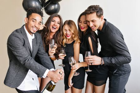 Handsome african man with beard opens bottle of champagne to celebrate something with friends. Indoor portrait of blissful young people spending time together at birthday party.