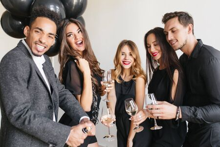 Pleased african man in tweed jacket holding bottle of champagne while his friends raising glasses. Indoor portrait of adorable dark-haired woman enjoying wine with boyfriend at party.