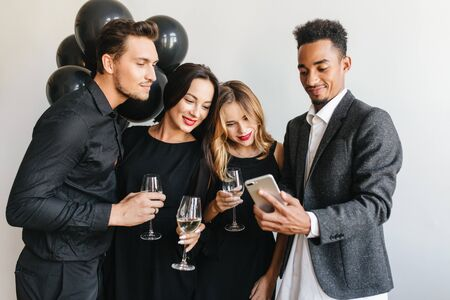 Confident african man in stylish gray jacket making selfie on event with colleagues. Pretty blonde girl looks with interest at phone screen during birthday party with best friends.