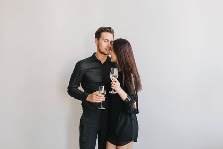 Long-haired brunette woman embracing her boyfriend while dancing at birthday party. Indoor photo of cute couple in black attires enjoying champagne and hugging on white background. 免版税图像