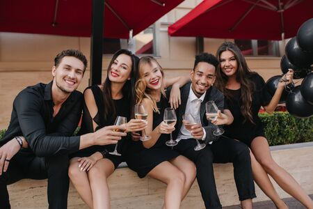 Inspired girls in beautiful black dresses posing in outdoor cafe with their boyfriends. Photo of laughing friends meeting at weekend and drinking champagne. 免版税图像