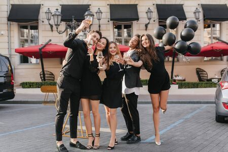 Full-length portrait of gorgeous brunette girl with balloons standing on one leg near restaurant. Outdoor photo of friends in black clothes posing with champagne after party. 免版税图像