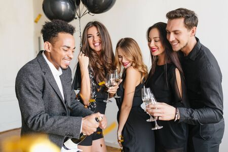 African man in formal attire opens champagne bottle with funny face expression. Refined curly fair-haired lady with trendy make-up holding wineglass during party with best friends.