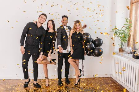 Indoor portrait of elegant woman in high heel shoes embracing boyfriend at party. Charming blonde birthday girl holding balloons and posing with african young man.