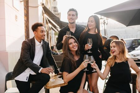 Joyful brunette man in black shirt looks away, holding glass of wine at party. Outdoor portrait of african guy in trendy jacket celebrating birthday with charming girls in cafe.