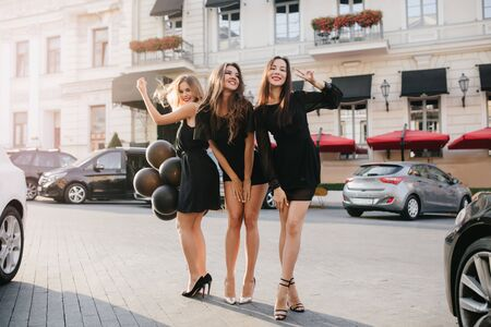 Full-length portrait of enchanting birthday girl in black dress posing with balloons at the street. Spectacular ladies having fun in city during summer vacation.