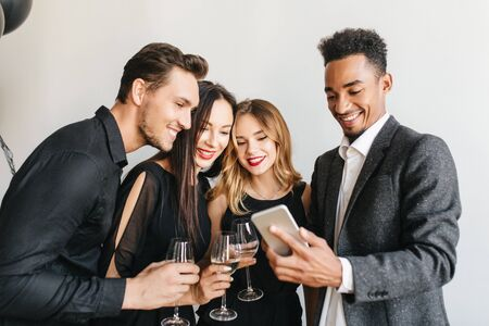Pleased african man in vintage tweed jacket making selfie with friends at birthday party. Indoor portrait of black guy holding smartphone and charming girls drinking champagne on event.