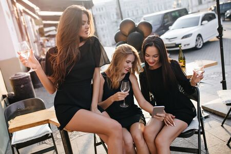 Magnificent ladies in black clothes sitting on chairs in outdoor cafe after exploring town. Portrait of glamorous girls relaxing in restaurant in sunny day.
