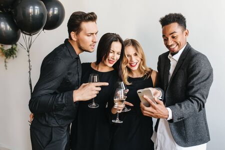 Joyful african man making funny face posing at birthday party with gorgeous girls. Attractive ladies with wineglasses smiling on white background while black guy taking selfie.