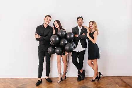 Full-length portrait of girls and boys with party balloons preparing house for event. Indoor photo of two loving couples posing on white background after double date. 免版税图像