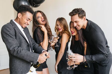 Smiling african man in stylish jacket opens bottle of champagne at office party. Long-haired female model dancing on white background with balloons while her friends posing with wineglasses.